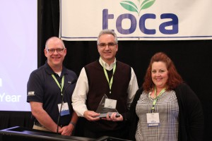 Howard Richman (center) is honored with the 2015 Plant Health Writer of the Year Award.  Scott Hollister, Editor-in-Chief of GCM Magazine, and Patty DiMucci of Bayer present the award.